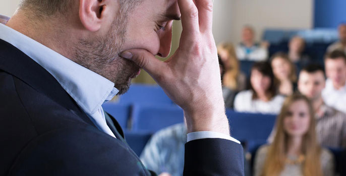 A man in front of a room holding his hand in front of his face in frustration