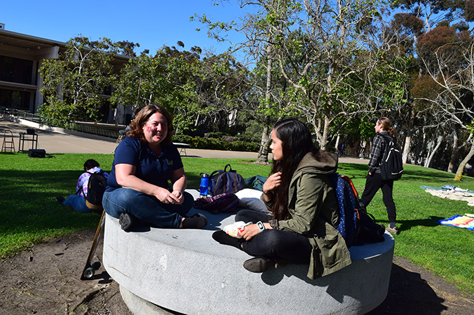 Two students sit on a round concrete bench on campus