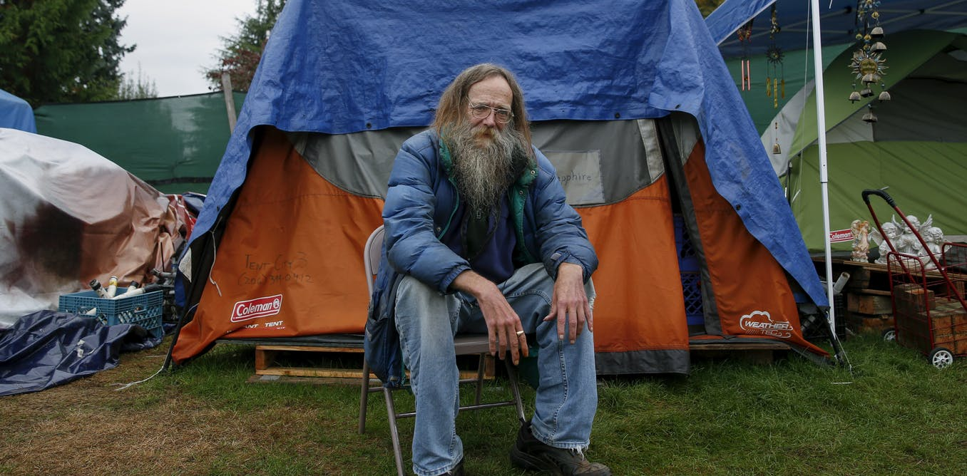 Lantz Rowland poses in front of his tent outside Seattle, Washington.
