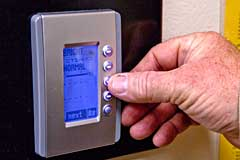 hand adjusting a thermostat