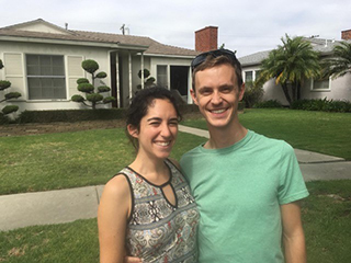 Stosh Ozog and Miriam Rubensen stand in front of a house.
