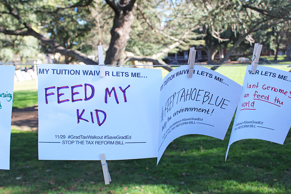 Signs displayed saying 'My tuition waiver lets me...' with answers such as 'feed my kid' filled in.