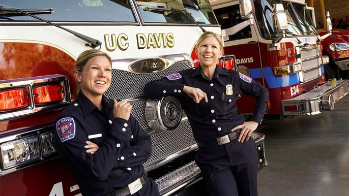 Twin firefighters pose in front of a fire truck