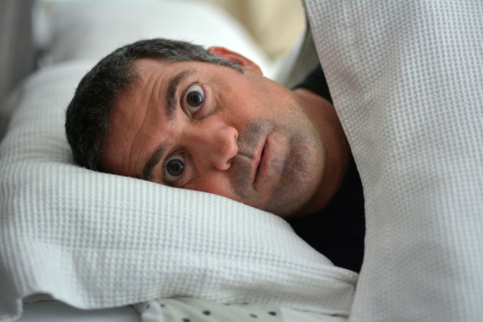 Man in bed looking surprised and scared