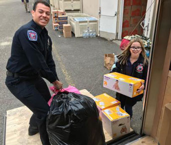 Student firefighter and young girl load trailer