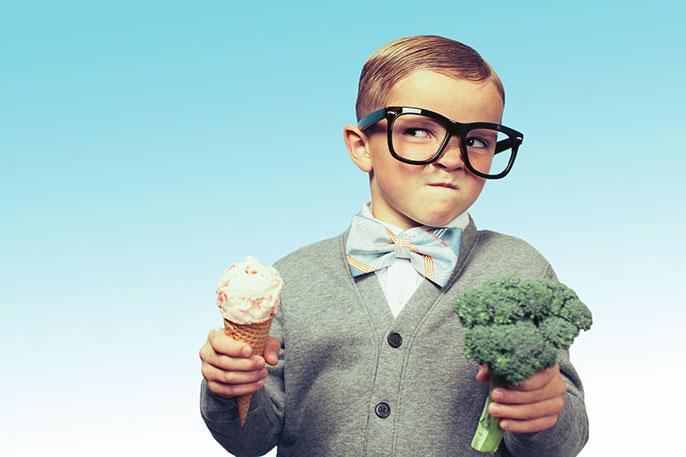 Mischievous boy holds ice cream and broccoli