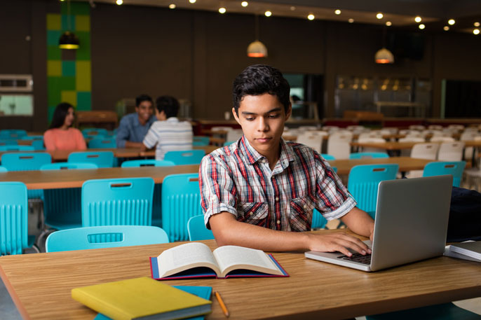 Male student typing on computer from book