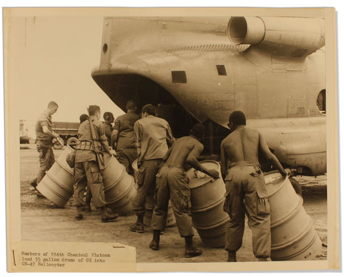 Men load barrels onto a helicopter