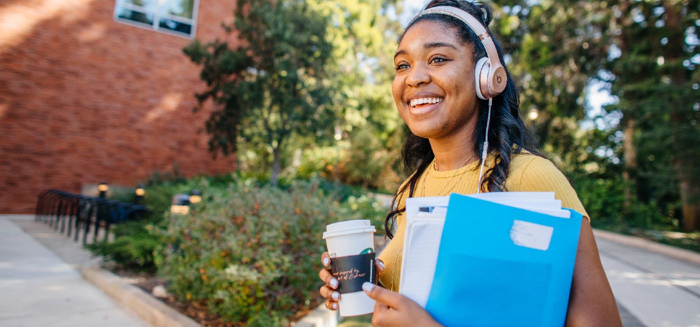 A student on campus, smiling, wearing headphones, holding a coffee and a folder of papers