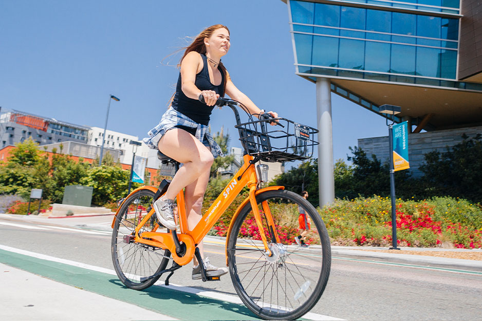 A student riding a bikeshare bicycle on campus