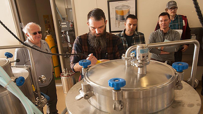 Professor Charlie Bamforth, left, and brewer Joe Williams, second from left, confer as beer is brewed in the UC Davis brewery.