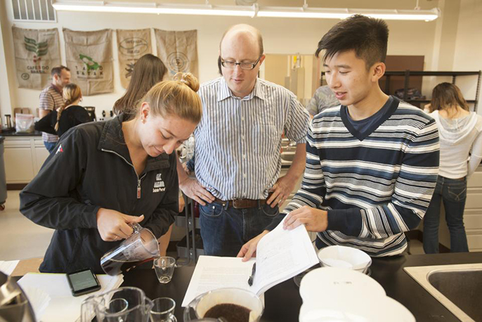"Associate professor William Ristenpart talks with Sabrina Perell, community regional development major, and Kyle Phan, an undeclared major, about the taste of their brew during a UC Davis ""Design of Coffee"" class in 2015. UC Davis is now establishing a Co"