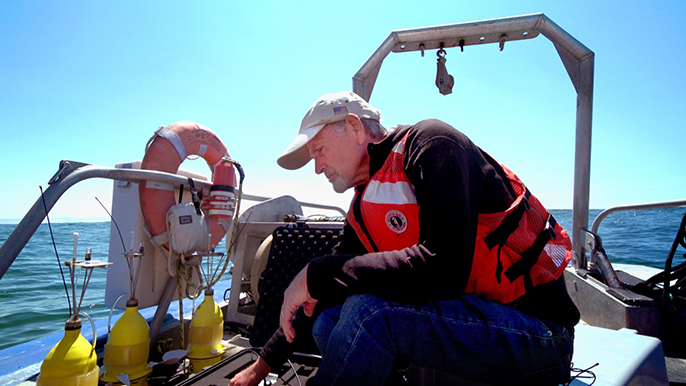 "UC Davis professor and marine ecologist Steven Morgan prepares to deploy yellow ""robot larvae"" off the coast of Bodega Bay."