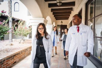 Image of University of California Health health professional students walking in outdoor courtyard.
