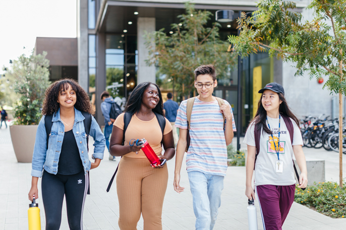 Small, diverse group of students walk across the UC Irvine campus