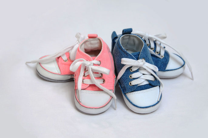 Baby girl and baby boy shoes next to each other