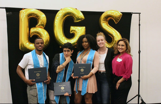 UCLA Guardian Scholars stand for a photo with their diplomas