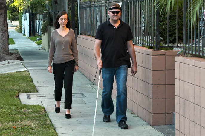 A man with a cane walking with a woman just behind him