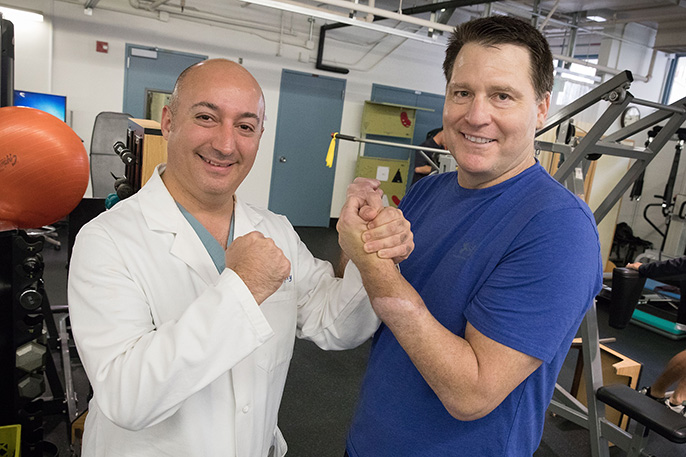 Dr. Kodi Azari, director of the UCLA Hand Transplant program, gets a good grip on Jonathan Koch's transplanted hand. Azari led the surgical teams that amputated Koch's hand and later transplanted a donor hand.