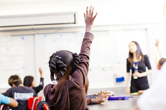 child raises hand in a classroom