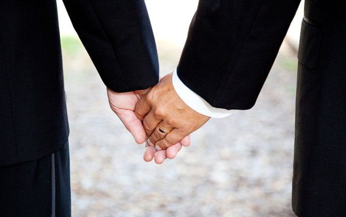 newlywed men hold hands
