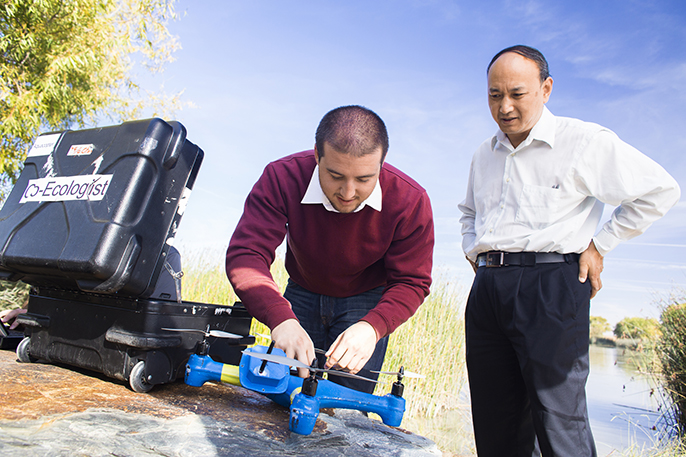 UC Merced professor YangQuan Chen (right) and student Brendan Smith work with drones.