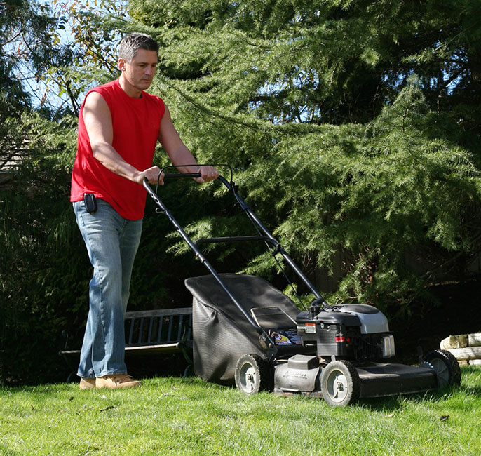 man using lawnmower