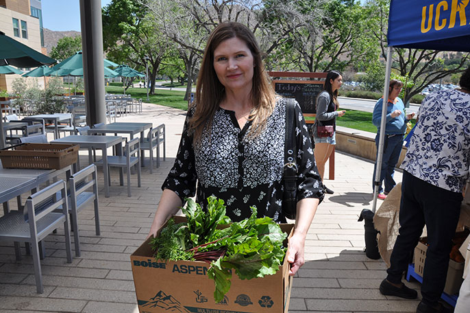 Dana Taylor picks up her produce at inaugural FarmShare event.