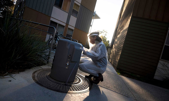 A woman in PPE tests wastewater on campus