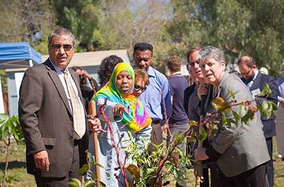 University of California President Janet Napolitano and UC San Diego Chancellor Pradeep K. Khosla listen as volunteer Karemah Alhark talks about the Ocean View Growing Grounds.