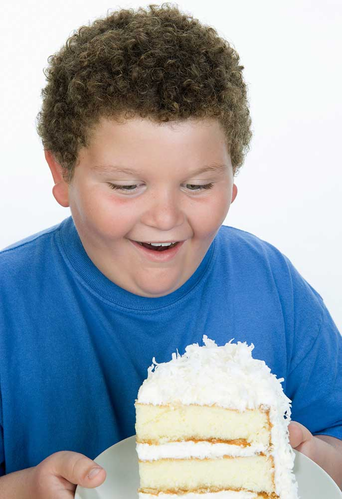 overweight boy with slice of cake (iStock)