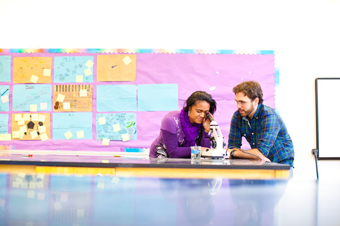 Teacher and student look through a microscope in front of a colorful backdrop