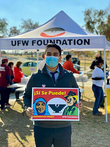Osorio holds up a UFW sign at a recent union event in Bakersfield