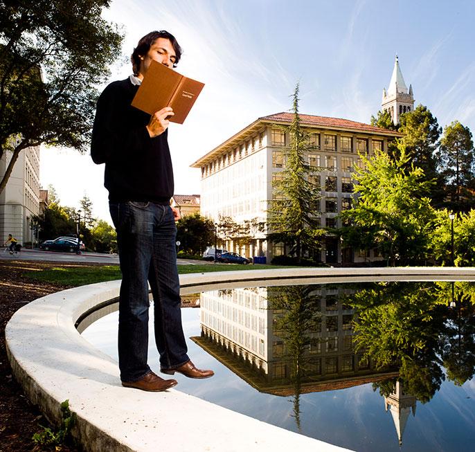 student reads book near Berkeley Campanile
