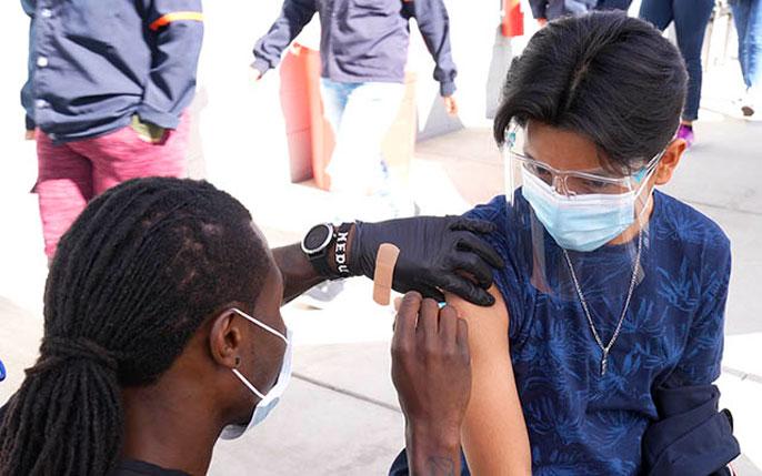 A worker receives a shot from a nurse