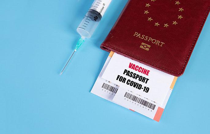 Passport next to a syringe
