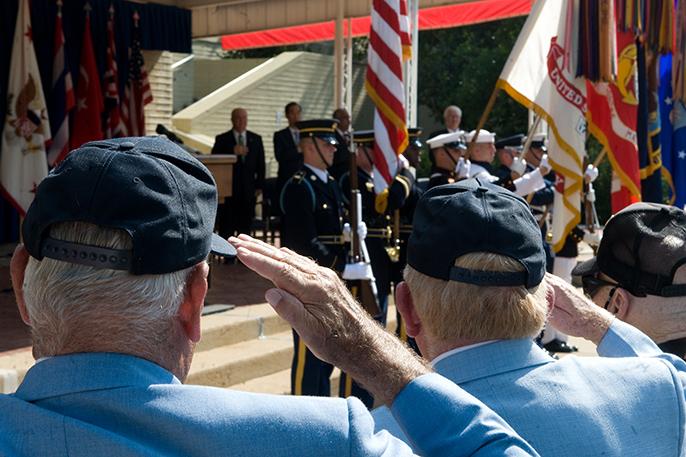 Korean War veterans saluting the American flag.