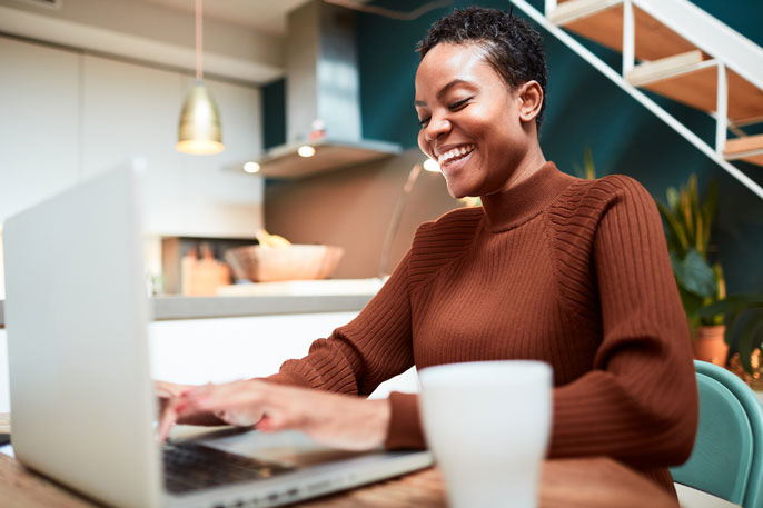 Young black woman laughing while looking at computer screen