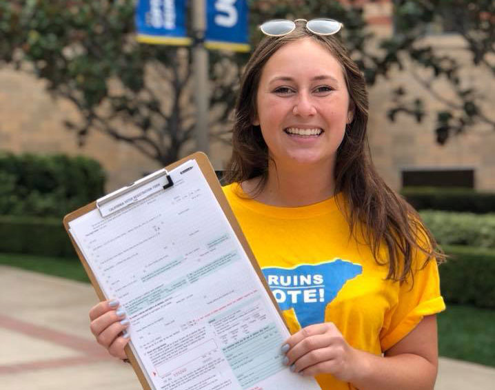 Young woman with Bruins Vote T-shirt holds up voter registration form