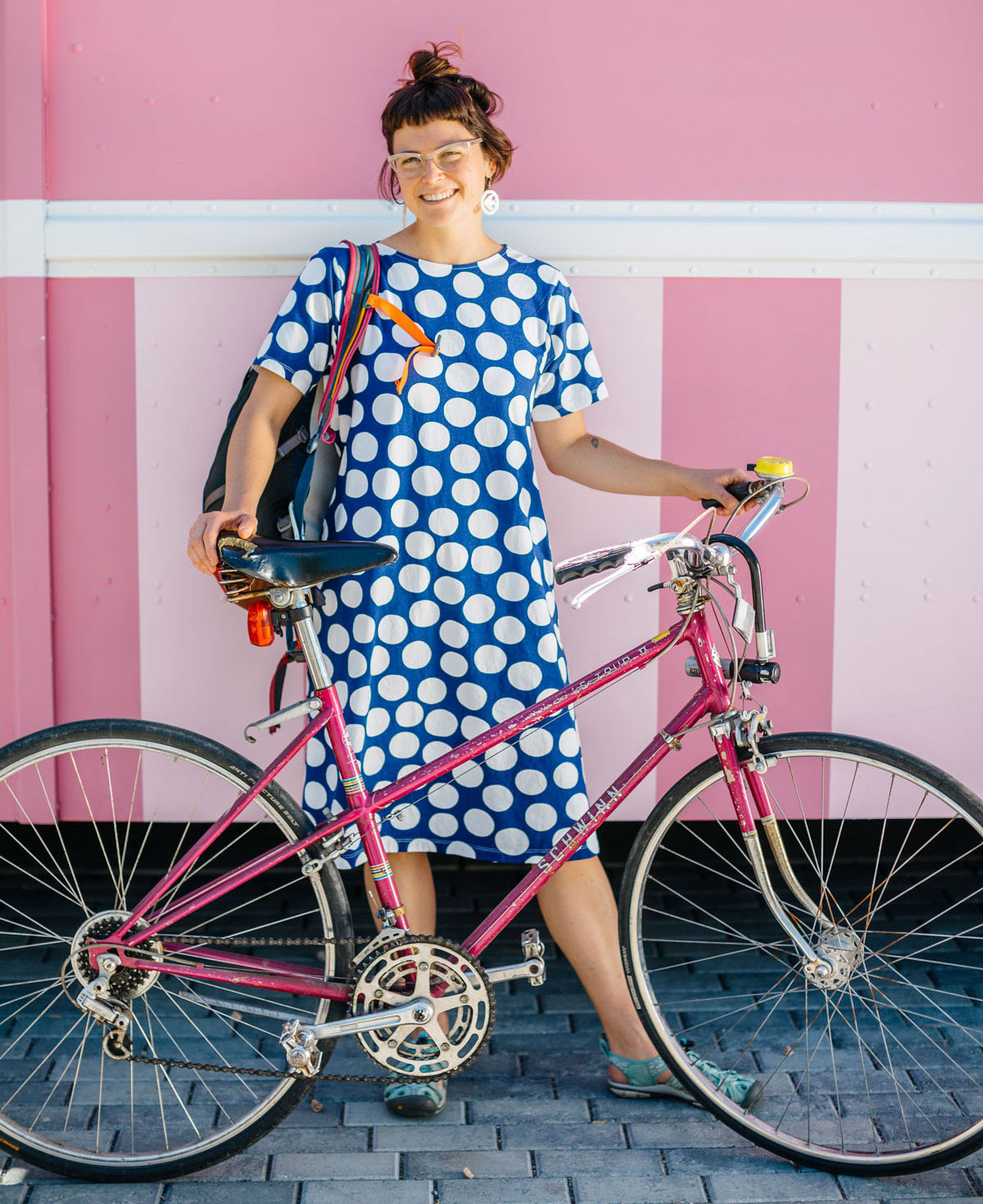 Woman holding bicycle and wearing a blue dress with white polka dots