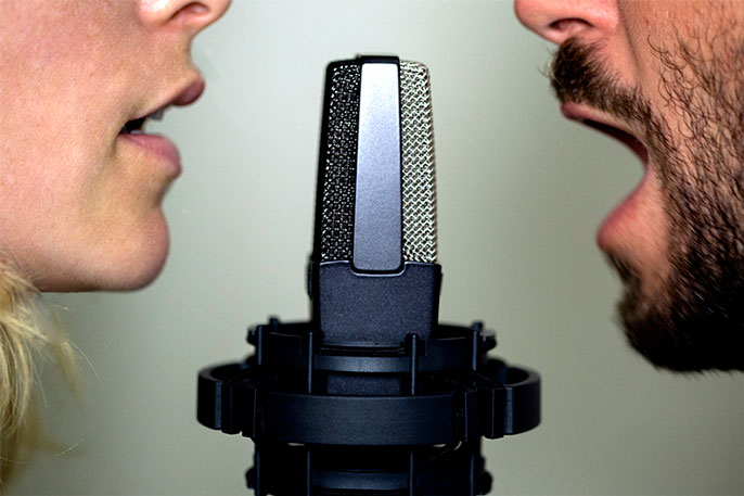 A man and a woman at a microphone