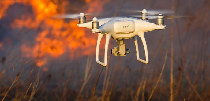 A drone with wildfire in the background