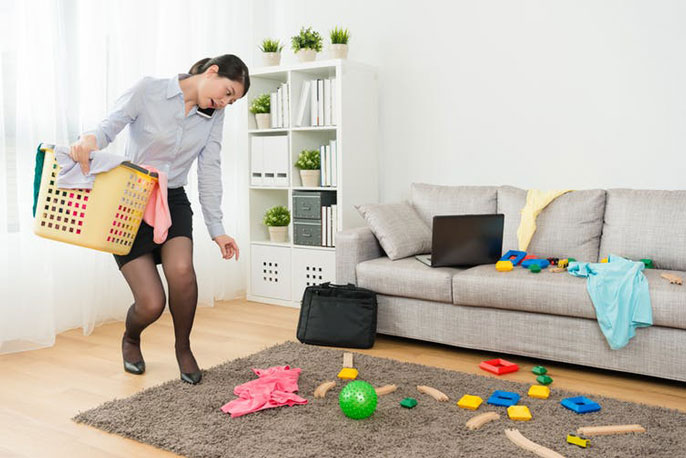 Woman picking up toys from floor