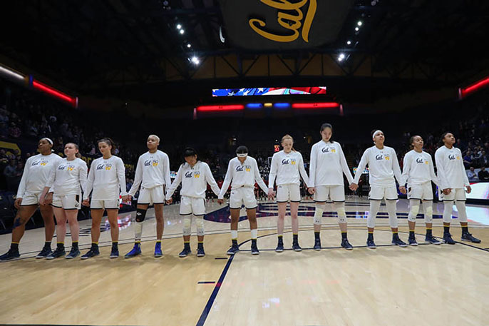 Women standing for anthem at basketball game