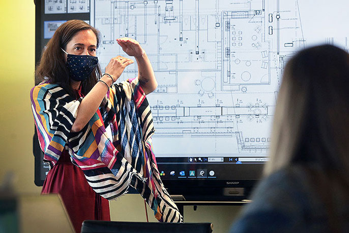 Woman explaining something in front of a large screen with architectural plans to a colleague