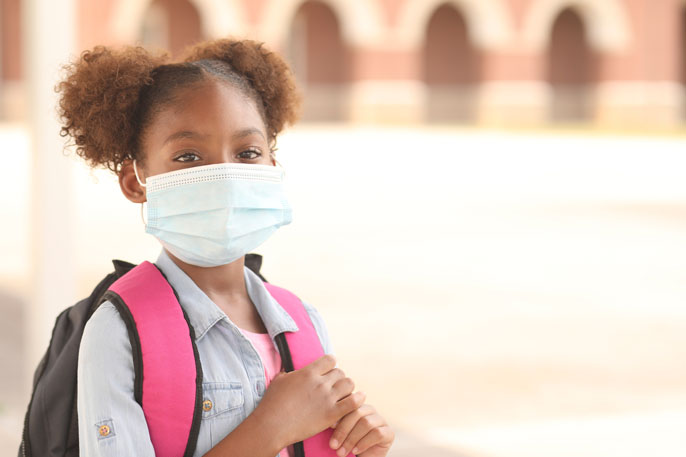 Young Black girl with a backpack in a mask