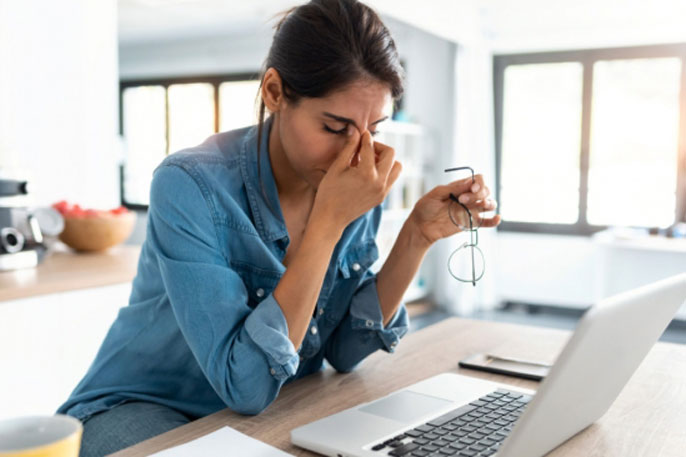 A woman rubs her eyes looking at computer